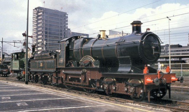 "With the tower block HQ of Nederland Spoorwegen visible in the background above, 3440 ""City of Truro"" was buffered up to the industrial 0-4-0T known as ""Kikker"" ( Frog, in English ), the sole surviving 100% Dutch steam locomotive despite looking very British!"