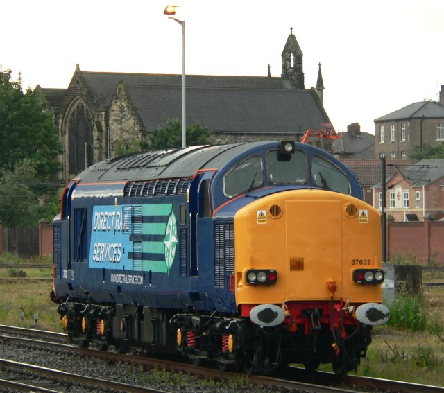 "37 602 makes an interesting comparison with 37 261, above, both being pictured at York by William Lyon Tupman and both in variants of Direct Rail Services livery. As seen on 6 July 2008, 37 602 is one of a number of alternator fitted Growlers originally refurbished for use on Channel Tunnel Nightstar services fitted with UIC jumper cables and designated as subclass 37/6. Built by English Electric at the former Robert Stephenson Hawthorn works at Darlington as 3209 / 8328 and outshopped in November 1962 as D6782, the 1750 bhp Co-Co was first allocated to 50B Dairycoates depot in Hull and was renumbered as 37 082 in February 1974. Refurbishment to 37/5 standard came in March 1986 and naming as ""British Steel Teesside"" in March 1987."