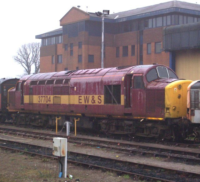 In its scruffy EWS livery, 37 704 was captured behind Platform 4 of Gloucester station on 20 February 2008 en route to storage at Long Marston. The 37/7 had previously been numbered 37 034 from March 1974 before refurbishment in January 1987. As D6734, Vulcan Foundry 2897 / D613 had been allocated new to 50B Dairycoates in March 1962.