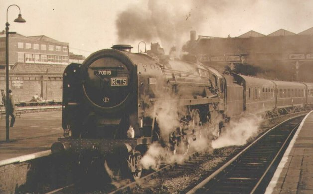 "With a full head of steam lifting the safety valves, 70015 ""Apollo"" starts a Railway Correspondence and Travel Society railtour from Manchester Victoria station on 19 March 1967."