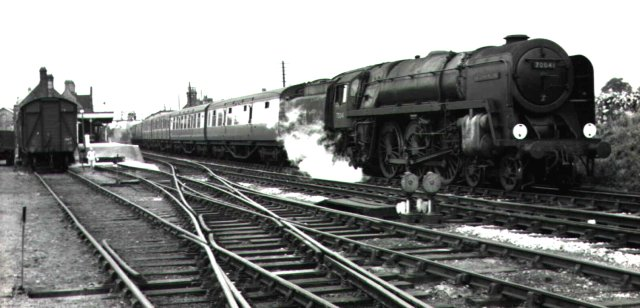 "With steam shrouding its exhaust injector, 70041 ""Sir John Moore"" hauls an express passenger train away from Thetford towards Norwich in this Roger Carpenter image from 1958."