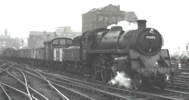 British Standard 4 4-6-0 75005 with a smaller capacity Riddles designed tender heads a Class 6 express freight train, largely composed of sixteen ton mineral wagons of the type built by the Gloucester Railway Carriage and Wagon Company