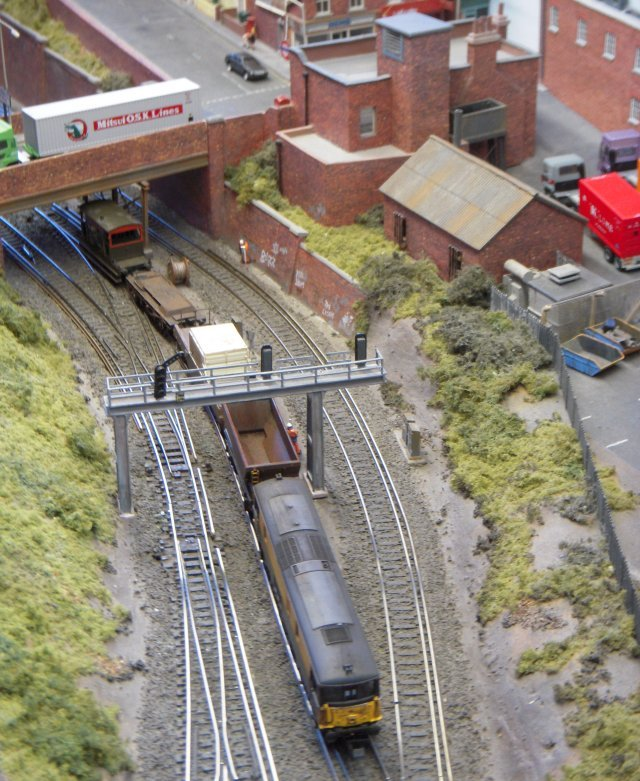 This layout was set in South London suburbia during the early 1990s Network South East period of operation with dc electrified third rails. It featured typical Southern stock of the era including EMUs, a Class 33 diesel electric and Class 73 electro-diesels - nowadays more associated with the Dean Forest Railway. All the buildings were scratch built - mainly from cardboard and mostly based on real buildings from around the area either adapted to suit the layout or as they really stood. Also featured were an electricity sub station and a Gatso speed camera. The small single baseboard allowed Hedges Hill Cutting to be stored in a loft and operated by one person.