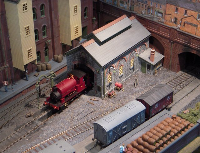 "Egypt Brewery was an attempt to present an industrial scene in an exhibition context with potential for both shunting and through running from one hidden area to another.  The brewery buildings - with main brew house to the left and boiler house and cooperage in the centre - were constructed from the American DPM modular system with a warehouse behind the small locomotive shed.  In the foreground the entrance was flanked by the main brewery offices and the gatehouse.  Locomotives were mainly derived from brass kits by High Level and Agenoria and most had 97:1+ reduction gearing for enhanced slow running.  Many also had appropriately ancient Egyptian names such as 0-6-0ST ""Nefertiti"" seen on shed below."