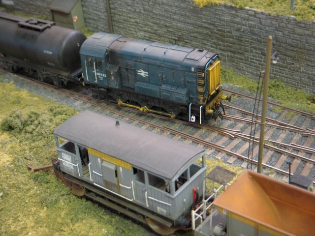 "Blue liveried 08 623 hauls a pair of two axled oil tank wagons out of Frampton Yard past a ""Shark"" ballast plough fitted brake van at the end of a short Civil Engineer's train"