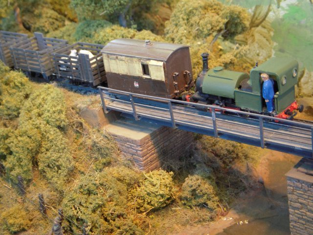 "Livestock is taken to market across the bridge behind a brake van still in Great Western Railway markings and hauled by a locomotive suspiciously like Sir Haydn from the 2' 3"" gauge Talyllyn Railway."
