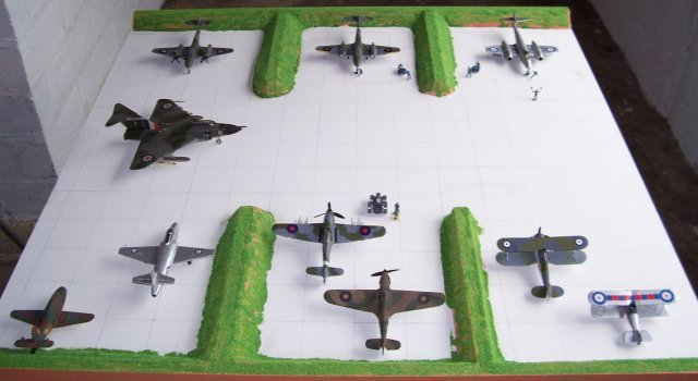 As described in the article on the design and building of the Square Airfield, prior to delivery of the diorama to Gloucester Folk Museum the opportunity was taken to lay out the aircraft models involved to see how much space would be left for the addition of airfield vehicles and figures. This simulation - in a well lit garage - also allowed individual aircraft to be recorded in what turned out to be largely the same positions as the Folk Museum were to finally chose for them.
