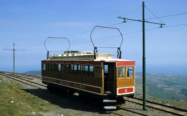 "The Snaefell Mountain Railway was built by a private consortium in just seven months in 1895 and was sold in the following year to the Isle of Man Tramways and Electric Power Company.  The five mile line -- starting from Laxey Village - was built to a track gauge of 3' 6"" as opposed to the 3' of the Isle of Man Railway which had opened between Douglas and Port Erin in 1873.  To allow the Manx Northern Railway 0-6-0T locomotive ""Caledonia"" to haul rails to the summit, a third rail was installed, as it was again in 1995 for the Centenary celebrations which also saw ""Caledonia"" reach the summit once more.  The Snaefell Mountain Railway - including gradients as steep as 1 in 12 - is the only electric mountain railway in the British Isles and still uses the six original tramcars from 1895 - each fitted with a distinctive Hopkinson bow collector on the roof to make contact with the overhead catenary.  This wiring is taken down each winter to prevent frost damage, during which time a diesel railcar can still run to the summit."