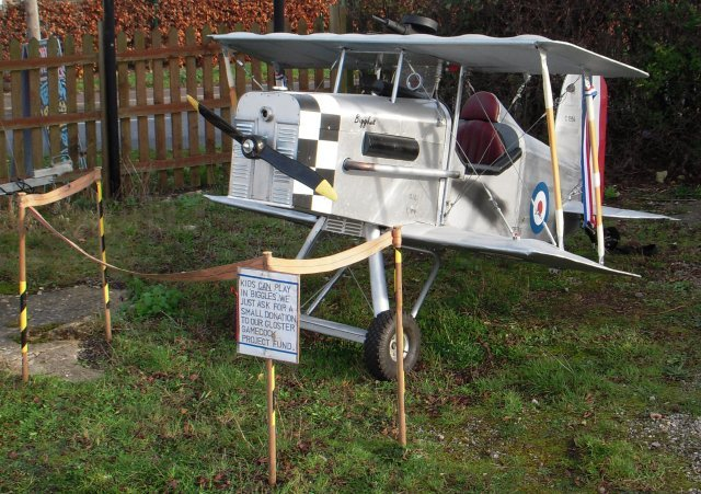 """Kids CAN play in Biggles,"" read the sign,"" We just ask for a small donation to our Gloster Gamecock project fund""  In fact it wouldn't be a Jet Age Museum fundraiser without the little biplane, as ""Biggles"" regularly appears at air and transport shows and is a popular attraction with children.  Chris Radford and Keith Eagles constructed Biggles in 1995 over 12 weekends, initially as a publicity stunt to appear in the Gloucester Carnival parade mounted on top of a Range Rover. Chris's son Tom, aged 10 at the time, piloted the aircraft."
