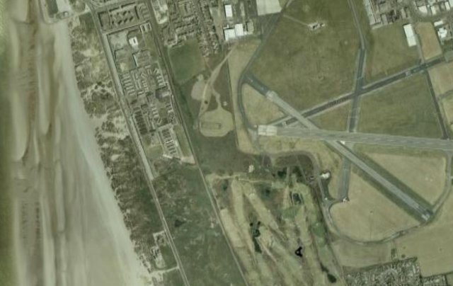 In planning such a layout, the question of vertical separation between trains and aeroplanes would also have to be addressed. For example, the passengers on the north-south coastal railway from Lytham St Annes to Blackpool South might be sometimes forgiven for ducking when an aircraft lands at or takes off from Squires Gate Airport (seen above ) as the strip of sand dunes that the line runs through is not far below the runway.  For this reason too there are no tunnels and few bridges nearby to hide any fiddle yards.  Other reasons why Squires Gate would be difficult to model would include the railway being single track ( limiting the  train traffic in an exhibition environment ), the airport buildings being on the eastern side of the airport ( making a coastal station illogical ), the distance between the railway and runway and the fact that the nearest airport hardstanding IS a runway, rather than a parking apron where static aircraft would most likely be seen.
