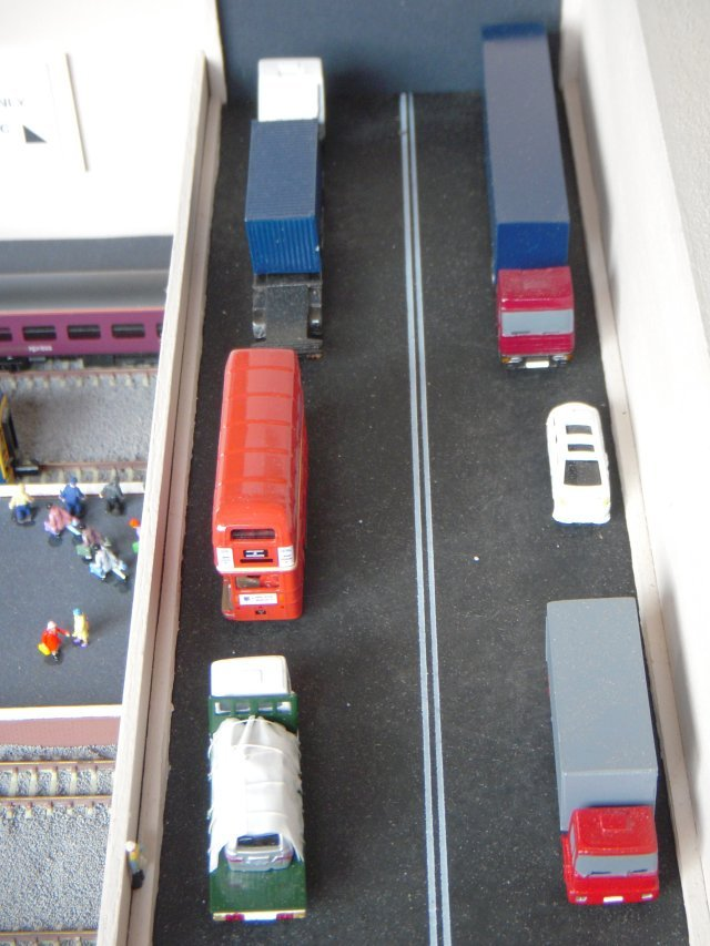 The road vehicles on the bridge were chosen to suggest that both an airfreight terminal and an airport bus station lay beyond the aircraft apron.  Nearest the camera are two MAN rigid wheelbase lorries from www.modelshop.co.uk with the flatbed on the left carrying a people mover body covered in tarpaulins and held down with rope.  In fact this effect was achieved with Rizla papers and thin cotton thread.  Like the Graham Avis Iveco articulated lorries nearer the portal, these MAN vehicles are one-piece castings with fixed wheels while the red AEC Routemaster bus is a die cast Oxford product with roling wheels - hence the need for it to be carried separately to exhibitions!