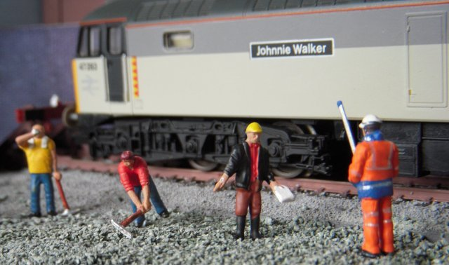 While the builder's gaffer waves a health and safety document at a surveyor during a frank exchange of views above, another railwayman is seen below on the scratchbuilt ground frame.