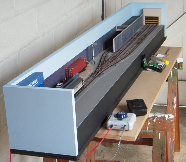 Pictured above is a typical scene in the garage whilst bringing Toucan Park to life , with control box, camera case, Woodland Scenics fine grey ballast, UHU glue, ballasting card and paintbrush joining the layout itself on the trestle. Each new round of developments were recorded for this feature and tested for continuing electrical efficientcy before work continued.