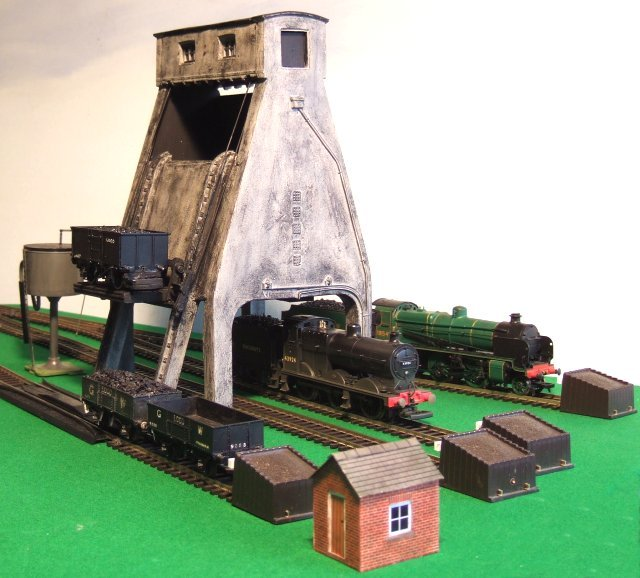 During the final decades of steam working, tall concrete coaling towers were built in many places. These discharged coal straight downwards rather than allowing it to be tipped in from the side and were filled by hoists. Loaded wagons would be lifted up and physically rotated at the top of the tower, as this model on Alan Postlethwaite's Brockley Acres layout demonstrates. Sadly all these concrete coaling towers have been demolished apart from the one at Carnforth ( formerly part of the Steamtown museum ) which was built by Italian prisoners of war in 1943.