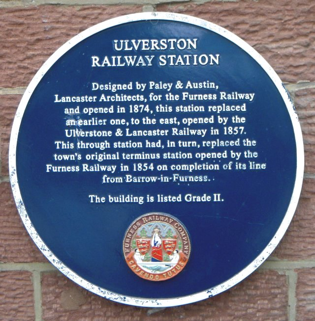 A plaque on the station building further explained that the Grade II listed structure had been opened in 1874, having been designed by Lancaster architects Paley and Austin as a replacement for an earlier one, located further to the east, opened by the Ulverstone and Lancaster Railway further to the east in 1857.  This through station had in turn replaced the first station in Ulverston, a terminus built by the Furness Railway in 1854.