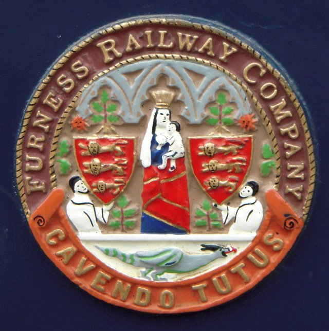Derived from the Great Seal of Furness Abbey, the Furness Railway coat of arms  depicts the Virgin Mary holding the infant Jesus in her left hand, whilst in her right hand she carries an orb, symbolising the world. She stands beneath the centre of three pointed arches and is flanked by two shields, each supported by a monk. Each shield is surmounted by sprigs of deadly nightshade, symbolising the valley in which Furness Abbey is built.