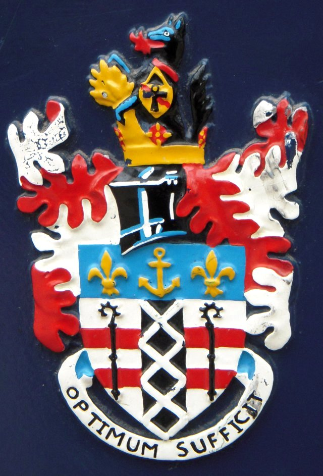 "In contrast to the Furness railway, the coat of arms of Ulverston, seen on the diamond shaped companion plaque, were granted as recently as 1 December 1955.  The shield expresses the ecclesiastical and manorial connections of the town and the red bars on white are part of the arms of the de Lancasters, Barons of Kendal and holders of Ulverston and Furness Abbey. The crosiers refer to the Abbey and to Conishead Priory, the black portion fretted with white is from the Harrington arms while the anchor and fleurs-de-lys are from the arms of the Barrow family. The anchor also occurs in the arms of the Gale-Braddylls of Conishead and is a reference to the former Port of Ulverston. The fleur-de-lys and their blue background also appear in the arms of the Dukes of Buccleuch, to whom the Manor descended.   The red roses are for Lancashire, the town having formerly been in that county, and the black wolf refers to name of the town ""Wulf-heres-tun"". The other emblems are for local industries; the agricultural market is symbolised by the gold sheaf, the flames are for the formerly important iron-smelting, the leather collar represents the tanning industry, the chain hanging from it is for the engineering industry, and supports a gold shield carrying a red lightning flash for the electrical industry and the Egyptian Ankh or Cross of Life, in green, for the anti-biotic manufacturing activities. The motto - OPTIMUM SUFFICIT, Only the Best Is Good Enough -  is based on that of the Barrow family 'PARUM SUFFICIT' - a little is enough."