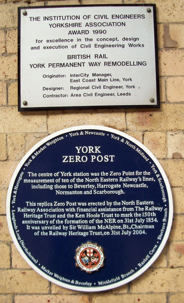 """York Zero Post. The centre of York station was the Zero Point for the measurement of ten of the North Eastern Railway's lines, including those to Beverley, Harrogate, Newcastle, Normanton and Scarborough. This replica Zero Post was erected by the North Eastern Railway Association with financial assistance from The Railway Heritage Trust and The Ken Hoole Trust to mark the 150th anniversary of the formation of the NER on 31 July 1854. it was unveiled by Sir William McAlpine,Bt., Chairman of The Railway Heritage Trust on 31 July 2004."" Around the edge of the circular plaque are the following railway company names: York & Newcastle, York & North Midland, York & Scarborough, Sherburn Branch, Raskelf Curve, Micklefield Branch, Market Weighton & Beverley, Longlands Loop (Northallerton), York & Harrogate, York & Market Weighton."