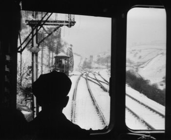 The poster picture for 2015 was taken in April 1961 during a snow storm on the Midland main line near Millers Dale.   An endearing feature of the very first diesel multiple units was the glass partition behind the driver's compartment and the silhouetted cap here helps to frame the junction to Buxton.  The train had connected with an express from St Pancras to Manchester Central which included an LMS 12-wheel dining car. These lovely lines through the Peak District closed under the Beeching axe.