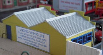 Similarly the paint scheme is in similar Swedish national colours to those used by Ikea and were achieved with Humbrol colours 81Matt Pale Yellow and 14 Gloss French Blue. The interior of the building was Humbrol 33 Matt Black and six-foot-way wooden decking left over from the Dapol Level Crossing was used both as a fence between Viking Vehicles and the level crossing itself and to divide the servicing bay from the shop. Combined with the tyre and spare part decal for the window, this left the shop suitably dark that a lack of counter, till, customers, shelves etc. would not be noticed.