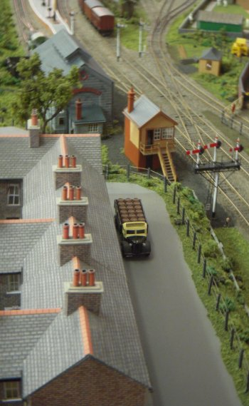 Wardton was a fictional terminus somewhere on British Railways Western Region. Originally part of the GWR, it featured a two platform station, a goods yard and shed and a separate siding for a local factory. The track and points were Peco with signals built from MSE kits and components, operated by servos controlled by Heathcote boards. The signals were not interlocked with points and so safe train operation relied on the vigilance of the operator!. Buildings were mainly plastic or card kits with extra detailing while the goods shed was scratch built due to limitations of space.