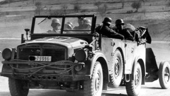 "Other utilitarian vehicles include the 60 bhp six wheeled Krupp Protz Kfz 69 (Kraftfahrzeug translating as motor vehicle) modelled here with a boat trailer but more often used as an artillery tractor (monochrome image with one wheelset raised to reduce tyre wear) and the four wheeled Kubelwagen. Literally translated as a ""bucket seat car"", this was designed by Dr Ferdinand Porsche and developed from the Volkswagen Beetle. Although lacking the four wheel drive of its Allied equivalent, the Willy's Jeep, the Kubelwagen's flat underside meant that it could be scooted along in deep sand or snow to keep up with armoured units."