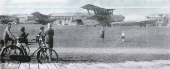 Early in the Second World War, a number of airliners commandeered by the British Government visited the Gloster Aircraft airfield at Brockworth, it is believed to pick up supplies for the British Expeditionary Force in France. Two Handley Page HP42 four engined biplanes can be seen just behind the bicycles while to the right is a Short Scylla single finned biplane and an Armstrong Whitworth Ensign monoplane.