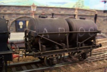 "This 0 gauge wagon - seen on Duncan Croser's Lynton Road layout displayed at Cheltenham GWR Modeller's Group Exhibition in aid of CLIC Sargeant in October 2008- was made from the JPL kit and represents a wagon built by Cravens of Sheffield in 1927 with twin tank barrels, each mounted on two wooden saddles. As such it makes an interesting contrast to the alternative arrangement of two parallel tanks running the full length of the chassis. Very similar in format to the tank wagons used by railway companies to supply compressed coal gas to carriages within trains and outlying depots, these ""long but thin"" twin tank wagons were sometimes used to carry petroleum but more often small consignments of more than one grade of edible oil."