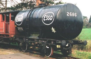Although at first glance a long way from the 100 ton bogie tank wagons introduced from 1969, Esso wagon 2686 - preserved on the Severn Valley Railway as a water carrier for fire fighting - has its 4 000 gallon liquid vessel anchored to the underframe by two fabricated steel saddles on either side of a riveted cradle carrying the oval worksplate depicted below. Unlike the 1902-1905 pattern cylindrical tank wagons there are no end stanchions, horizontal beams, tie bars or wire ropes. It has a 35 ton gross laden weight.