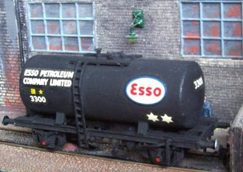 "Having featured Esso wagons in both Class A and B categories, mention must be made of arguably the most famous tank wagon ever to appear as a 4mm scale injection moulded kit. First marketed by Airfix, Esso Class B wagon 3300 is now sold under the Dapol banner. In comparison with some of the other designs discussed above this wagon has a simple yet elegant twin-saddle attachment between cylinder and chassis although the 22' 6"" cylinder noticeably stops short of the full length of the chassis ( 27' 9 3/4"" over buffers ) and is far enough inside the loading gauge to permit sub-solebar length ladders to be attached amidships. Other visible refinements include roller bearing axle boxes and two brake blocks acting on each wheel. The latter were applied either by manual lever during shunting or by twin vacuum cylinders as part of a vacuum brake fitted train. Like later airbraked monocoque tank wagons, the buffers were either hydraulic or pneumatic."