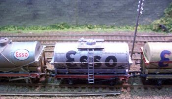 Three models on Barnhill Model Railway Club's EM gauge Kingsfield layout show the evolution of railway tank wagons designed to carry Class A inflammable liquids such as petrol. All three Esso marked vehicles use the cradle method of supporting the cylindrical tank but the older pattern wagon on the left - with the blue edged oval logo - has the crossed wire ropes used until the mid 1920s. The wagon on the right - with large blue corporate lettering edged in red - is in the light buff livery with red lining stipulated from 1902 to March 1939 while the wagon in the centre of the rake has the overall silver used from 1945 onwards. Although out of shot, these Class A wagons were correctly coupled to low sided wagons to distance them within a train from both locomotive and guards van.