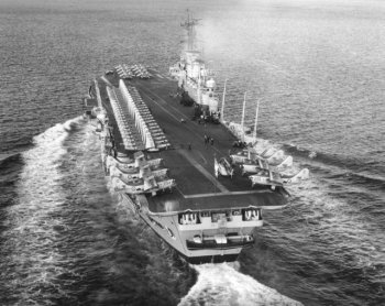 Similarly, the fourth HMS Ark Royal of the Royal Navy – pennant number R09 – took naval aviation into the jet age as the first ship to be constructed with an angled flight deck and steam catapults, as opposed to having them added after launching. The angled flight deck allowed any aircraft attempting to land but failing to engage its arrester hook with the trapping wires at the stern to take off again rather than face being caught in a crash barrier net stretched across the deck to prevent collisions with aircraft parked further forward. It also allowed aircraft to be launched and recovered at the same time. Catapults fed with steam direct from the ship's boilers also allowed heavier aircraft to be launched faster and a mirror landing system replaced the deck landing officer with his illuminated bats so that jet pilots could react faster when attempting to land. At the stern are six Fairey Gannet aircraft, in this case anti-submarine variants without the belly radome of the airborne early warning type.