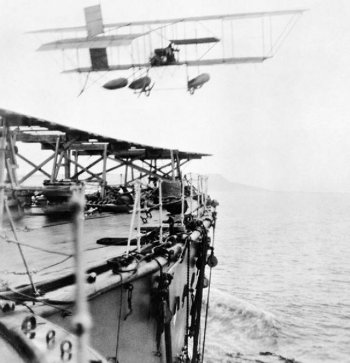 Most types of modern helicopter can now fly faster than the biplane seaplanes of the two World Wars, but the challenge of launching - if not recovering - a higher performance aeroplane from a moving ship was first embraced by the Royal Navy over a century ago. Commander Charles Samson, became the first airman to take off from a moving warship when, on 2 May 1912, his Short S27 left the battleship HMS Hibernia while she steamed at 10.5 knots during the Royal Fleet Review at Weymouth.