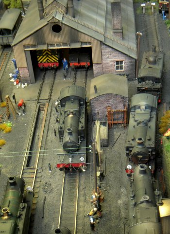 This diorama shows different ways of filling locomotive bunkers with coal. Centre-piece is a great concrete 'Centotaph' tower with an electric wagon hoist and balance weights at the front. This is modelled in O gauge with an LNER 0-6-2 class N1 tank which runs to a shed with a flat water tank on its roof. In front is a ramped coaling stage in OO gauge with a small tank engine. A class WD 2-8-0 runs from here across the ashing pit to a manual coaling stage with crane. There are samples of G, Z and T gauge track on the right and photographs of real coaling facilities on the backscene. The outside loop has an N gauge coal train headed by a GWR tank. A surreal touch is provided by a Rhine coal barge and swimmers who climb the Cenotaph to a roof-top lido. Visitors may operate the locomotives. Dimensions are 5 ft 4 in x 1 ft 8 in.