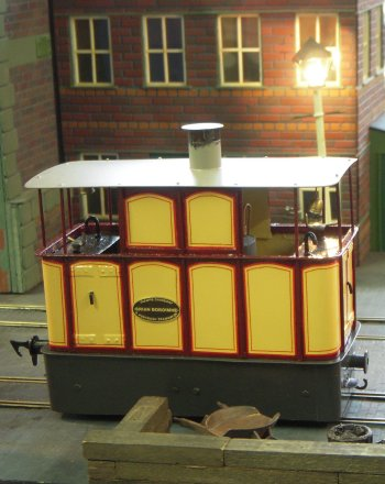 Electric pick-up was through the wheels - the overhead line being a dummy. The trams - made of brass with Slater's wheels and coreless motors - were scratch-built, modelled from scale plans and many, many photos: each taking some 3 to 15 months to construct.  Layout  dimensions were 15 ft x 2 ft.  In particular I liked Works Car 24, essentially being a five plank open wagon with a driving cab cantilevering out from each end and held together with a longitudinal bar supporting the trolley pole.  It is pictured above between a service passenger tram and a nun praying at a shrine to the Virgin Mary.