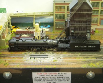"""This layout was intended to represent a fictional but plausible """"New Mexico Railroad Museum"""" in the city of Santa Fe, in reality only served by a narrow gauge railway until the 1940s when the line from Antonito was abandoned.  The layout assumed that the narrow gauge railway survived and still serves both the Museum and local industries.  In contrast the preserved standard gauge locomotives just paraded about, giving the operators the chance to run anything they liked!  The flexible track was commercially available but the points were hand-built, soldered onto copper-clad sleepers. Control was Digitrax with sound and the layout measured 9 ft x 1 ft 4 in."""