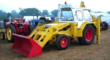 "Although not providing an exact like-for-like comparison with the model - first offered in 1963 as a load for the Airfix ""Lowmac"" railway wagon - the McGurk 3C does display the JCB logo in some of the same locations and does boast the red buckets and wheels, albeit the rear wheels having a radial fin arrangement rather than hubcaps. The 3C also offers some clues about the correct location of trafficators, head and tail lamps and warning beacon. The most noticeable differences however are the size and complexity of the hydraulics round the still-slideable rear king post and the different design of cab, which in this case is painted white. The back window is larger, the windscreen is angled forward rather than back and the sides comprise a fixed rear glazed section and a tractor type door. This door is accessed by the driver climbing up steps on the rear wheel front mudguard although the corresponding section on the model is vertical with no steps and the side of the cab is formed of one big window. How the driver was supposed to get in is a mystery to me!"