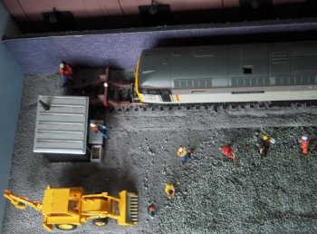 The figures in high visibility vests were metal and left over from Sulzer Gold Cup while the rest were by Bachmann, corresponding 2mm versions having already appeared on Terminal 1. The picture above also shows the coarse rubble defining the site of the old Toucan Park roundhouse against the fine ballast, which slopes up around both the hut and the running line.