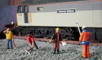 While the builder's gaffer waves a health and safety document at a surveyor during a frank exchange of views above, another railwayman is seen below on the scratchbuilt ground frame. Although the main Park Royal - Wembley route was controlled from a power box ( hence the low brick S&T building) by the 1990s the remote location of the depot made, to my eyes, a locally controlled ground frame necessary complete with lamp ( made from old Airfix sprue ) for night time arrivals and departures and a white telephone cabinet to allow the signaller to communicate to the next box or panel down the incline. With only - in effect - two points and two signals to control even a small signal cabin would seem too much to ask for at Toucan Park and such a structure might also have blocked the view of the moving locomotives in a way that a ground frame would not. A ground frame also had the advantage of being small enough to be placed right next to the point, avoiding the need for large amounts of rodding.