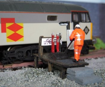 Although a similar ground frame was once available as R8732 in the Hornby Skaledale range, I decided to have a go myself after reading Paul A. Lunn's article in the August 2007 issue of Railway Modeller. The substructure was a piece of thin modeller's plywood measuring 36mm x 14mm with a deck on top measuring 40mm x 16mm and made of three sections of wooden coffee stirrer, as used in First Class on Trans Pennine Express and in many fast food restaurants. The six supporting legs were made from matchsticks, as were the two inset uprights for the track diagram board, also made from coffee stirrer. The lever frame was made from a single balsa offcut with grooves scored in it and three of the levers were made from plastic comb teeth. The fourth lever was the rod supplied with the Bachmann figure. Two of the levers were painted red for signals with the other two being black point levers. The three levers in the default forward position also had small dabs of silver to represent the handles and data plates. The heavily creosoted timbers were represented by an overall coat of black followed by dark brown to taste and the non slip tread was made from fine wet and dry abrasive paper. The stone steps up from track level were made from balsa and painted grey.