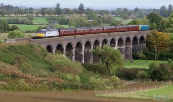 "Emphasising the 210 yard length of the 42' high 15 arch curving blue brick structure on 2 October 2010 was a train of six maroon Mark 1 carriages hauled by two tone grey 47 376 ""Freightliner 1995"" with blue liveried 47 105 bringing up the rear. This service, forming part of that year's Gloucestershire Warwickshire Railway Diesel Gala, marked the beginning of regular diesel hauled trains across the 1904 built viaduct which had returned to single line traffic in the Spring of 2010."