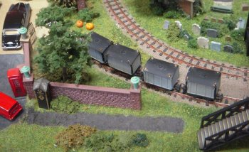 "A spooky addition to the October 2016 Cheltenham GWR Modeller's Exhibition for nearly Hallowe'en (and organiser Mike Walker's birthday!) Nicholas Wheatley's Journey's End' features an 009 gauge (4mm scale) narrow gauge railway serving a cemetery. It is entirely fictional, set ""somewhere in England"", though inspired by the London Necropolis Railway that ran from Waterloo to Brookwood, Surrey, from 1854 until 1941. The narrow gauge dimension was inspired by the Golden Valley Light Railway in Derbyshire, which runs from the Midland Railway Centre at Butterley towards a natural burial ground. The setting is almost timeless, but can be dated by use of different vehicles anytime from the present back to the 1950s."