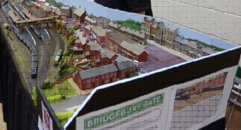 "Bridgebury Gate is a fictional town somewhere in the south of England at a time somewhere between 1966 to 2000. The layout is 148th scale - N gauge and consists of a twin track mainline passing a station with twin island platforms and limited freight facilities. Change here for trains to ""Mikel End"" a somewhat ancient branch line that survived closure by being reduced to single track – the remnants of the double track might still be visible. Round the back we have 6 lane fiddle yard - each line each holding 2 6/7 coach trains or one really long"