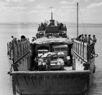 While the LCM could land one Sherman tank after a relatively short sea crossing, projecting large numbers of armoured vehicles into an opposed amphibious assault over a long distance required categories of vessel known as Landing Craft Tank – seen here – and the even larger Landing Ship Tank. The Landing Craft Tank (LCT) concept was created in 1940 by Winston Churchill himself who demanded a vessel capable of landing three Churchill heavy tanks directly on to a beach but be able to sustain itself at sea for at least a week. It also had to be easy and cheap to build. Naval architect Sir Roland Baker produced the initial drawings for the new LCT design in three days with Fairfields and John Brown ship builders developing the concept. The first LCT Mark 1 was launched by Hawthorn Leslie in November 1940 and featured a steel door behind the ramp to seal off the tank deck. The side bulwarks were also hollow and buoyant while fuel and ballast tanks in the double bottom allowed the Landing Craft Tank to be pitched back for beach landings. Key to operating the petrol engined LCTs was the stern mounted kedge anchor which stopped the vessel from slewing. As well as the existing winches to pull on the kedge anchor and haul the LCT off the beach, the Mark II LCT was longer and wider than the highly unseaworthy Mark I with more powerful petrol or diesel engines. The Mark III was shorter but wider while the Mark IV could carry six Churchill tanks. The American built Mark V could be transported in sections and assembled aboard a Landing Ship Tank and the LCT concept eventually evolved into the Landing Craft Medium, capable of carrying eight large tanks and 50 fully armed troops.