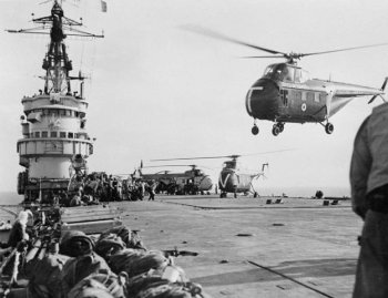 In this picture, Royal Marines are preparing to fly into Egypt aboard piston engined Westland Whirlwind helicopters from HMS Theseus.