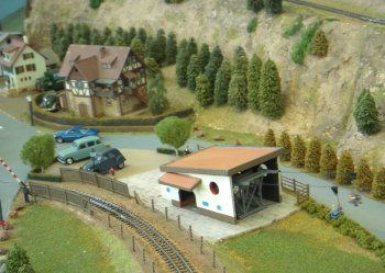 This layout was based loosely on an area close to the French-German border, within a National Park between Permasens and Landau, north of Strasbourg. The station midway at Hinterweild had a branch line which went up to an area called Altbahn. The branch line went over a level crossing, with working barriers. There was a chair lift that went to a higher level. All the loco stock was either French or German, with steam engines and diesel railcars. All the railcars were scratch built.