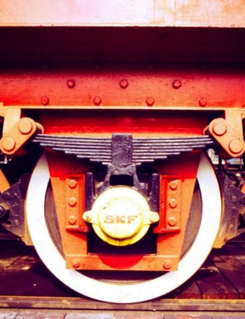 "Resistance to constant forward motion of any wheeled vehicle comprises several components including bearing friction ( reduced in the case of roller bearings replacing traditional white metal axleboxes ) , air resistance and rolling resistance. On a true railway vehicle, rolling resistance is of primary concern and occurs at the ""contact patch"" - the tiny coin-sized area at which the wheel tread is actually touching the rail."